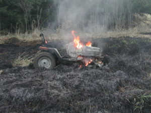Lawn mower on fire surrounded by burnt vegetation