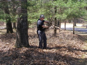 Resident remove dead branches from around their home to reduce their risk should a wildfire occure in their area.