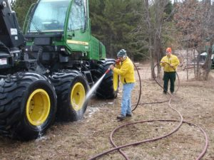 Forester hoses down logging equipment to remove invasive seeds.
