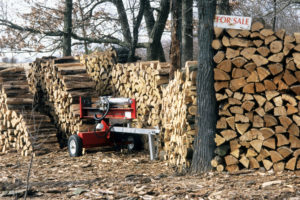 "A large stack of firewood with a sign next to it that says ""For sale."""