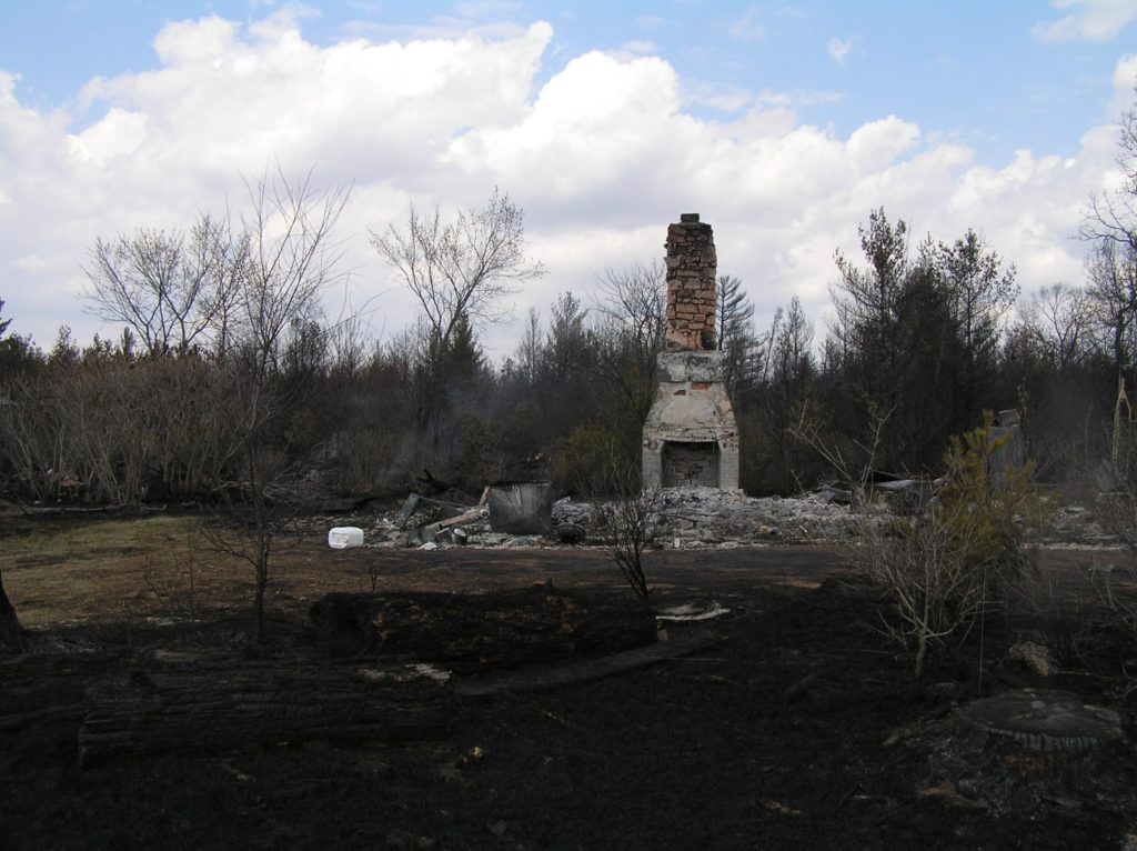 A house chimney remains after the Cottonville Fire destroyed the rest of the home.